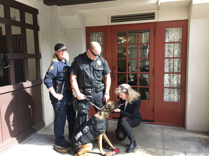 Riverside County Animal Control Officer Tiffany Fuller helped bring together Hemet PD Officer Matt Gomez and K9 Jack giving kisses to K9 Armor Cofounder Suzanne Saunders