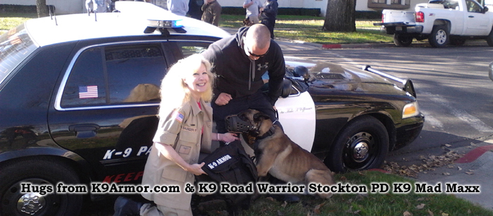 K9 Armor Co-founder Suzanne Saunders shakes paws with Road Warrior Stockton PD K9 Mad Maxx
