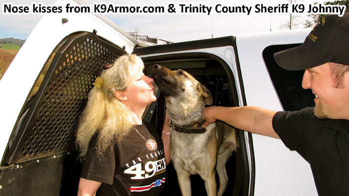K9 Johnny gives k9 kisses to Suzanne Saunders for his K9 Armor vest. with smiles from Trinity County Sheriff's Deputy Nathaniel Trujillo
